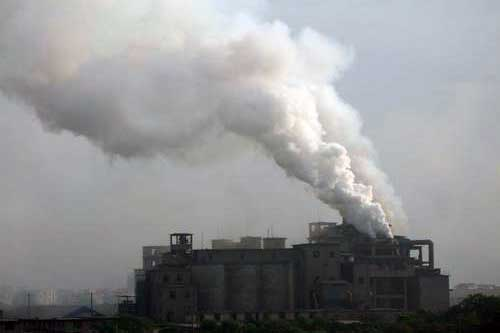 A cement plant in operation, emitting large amount of gas and dust.